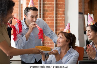 Birthday girl mature female sitting on chair surrounded by cheerful friendly multiracial colleagues wearing hats use party blower giving holiday cake congratulating happy birthday best wishes concept