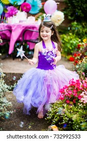 Birthday girl playing in the garden during a party in her purple tutu with star wand