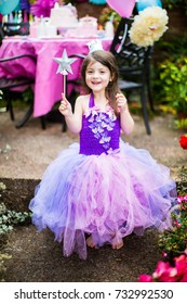 Birthday girl in purple and pink tutu dress having a unicorn princess themed party with wand