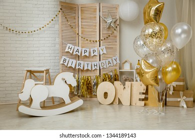Birthday gold and white decorations with gifts, toys, garlands and figure for little baby party on a white bricks background.