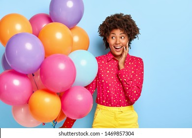 Birthday greeting. Positive lady with Afro hairstyle, gazes aside, has party mood during happy holiday, wears fashionable bright clothing, holds bunch of colorful balloons, feels great pleasure