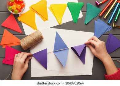 Birthday handmade background. Female hands making party paper decorations and colorful flags garland. DIY accessories on gray wooden planks, top view. Holiday organization, hobb, handicraft concept