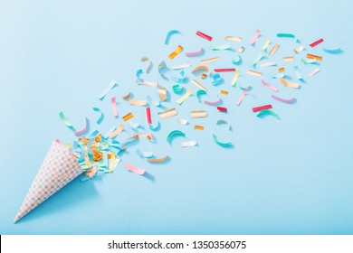 birthday hat with confetti on blue paper background