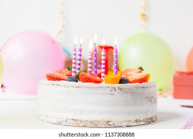 Birthday healthy yougurt berry cake with candles on colorful party background with bright party tools, decoration,. gefts and baloons. Happy holiday design concept. Selective fous, copy space
