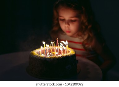 Birthday. A little sweet girl blows out candles on the stoke.