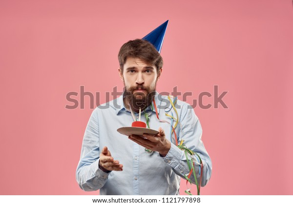 birthday man in a cap holding a cake on a pink background