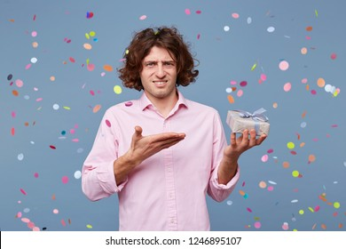 The birthday man was congratulated, he was given a gift, he stands displeased with a puzzled expression on his face and is pointing on a small box with a present in his hand.