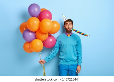 Birthday man meets guests with bunch of multicolored balloons, wears party hat, blows in horn, wears blue outfit, celebrates 30s anniversary, poses indoor. People, entertainment and holiday attributes