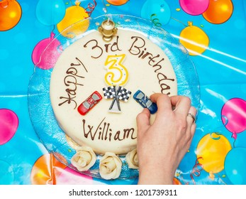 Birthday marcipan cake for a William with cars over blue table cover with yellow and pink balloons