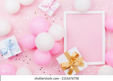 Birthday mockup with frame, gift box, pastel balloons and confetti on pink table top view. Flat lay composition.