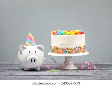 Birthday Money Concept with Rainbow Cake, one Candle and cute Piggy Bank over a neutral background.