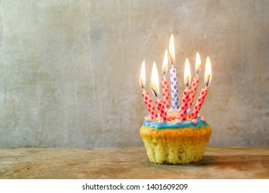 birthday muffin or cupcake with red and blue burning candles on a wooden board against a rustic wall, copy space, selected focus, narrow depth of field