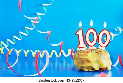 Birthday of one hundred years. Cupcake with white burning candle in the form of number 100. Vivid blue background with copy space
