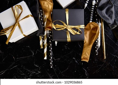 Birthday or Party accessories set with Gift boxes, balloon, candles in Gold, Black and White color. Flat lay, top view