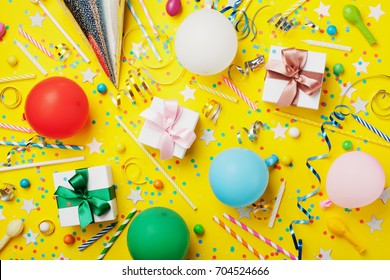 Birthday party background with balloon, gift, confetti, carnival cap, star, candy and streamer. Flat lay style. Colorful children greeting card.