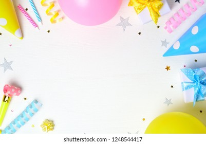Birthday party background with party hats, balloons and birthday gifts. Flat lay, top view, copy space.