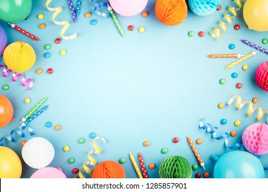 Birthday party background on blue. Top view. Frame made of colorful serpentine, balloons, candles and candies.