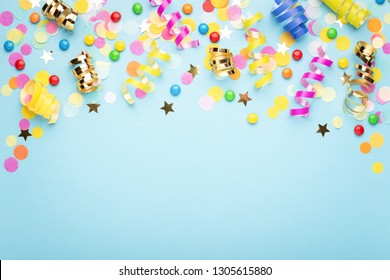 Birthday party background on blue. Top view. Border made of colorful serpentine, candies and confetti.