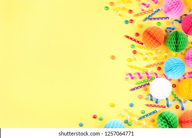 Birthday party background on yellow. Top view. Border made of colorful serpentine, candles, candies.