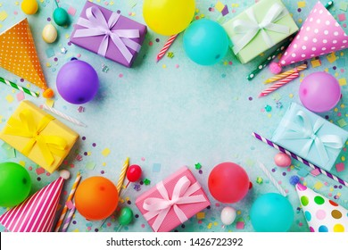Birthday party banner or background with colorful balloons, carnival caps, gift boxes and confetti. Top view.