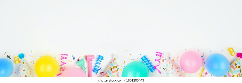 Birthday party banner with bottom border on a white background. Top down view with balloons, party hats, streamers and confetti. Copy space.