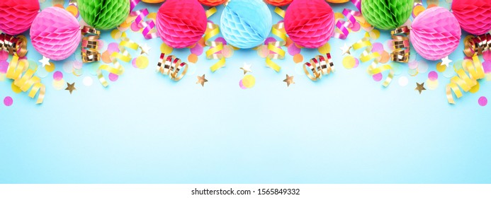 Birthday party banner on blue. Top view. Border made of colorful serpentine, balls and confetti.