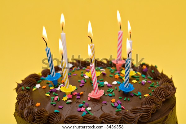 A birthday party cake with lit candles and sprinkles.