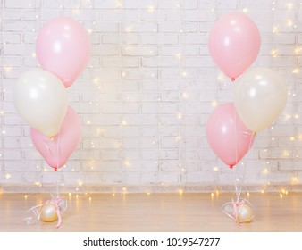 birthday party concept - brick wall background with lights and pink balloons