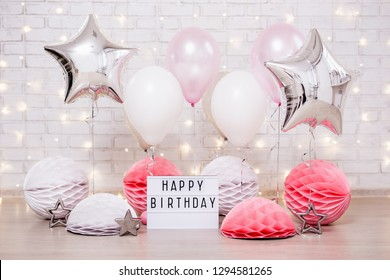 birthday party concept - close up of air balloons, paper balls and lightbox with happy birtday text over brick wall with lights