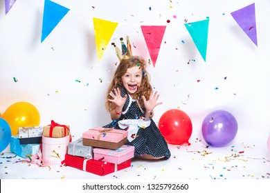 Birthday party for cute child. Little girl throwing colorful confetti and looking happy on birthday party
