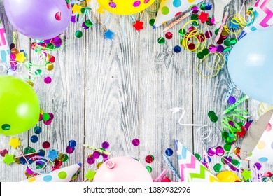 Birthday party decoration background with balloons, gift boxes, steamers and confetti, wooden white table copy space above