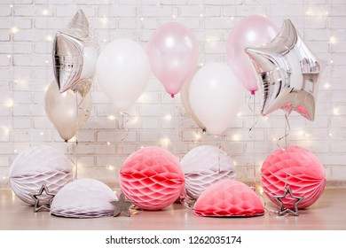 birthday party decoration - close up of colorful air balloons, stars and paper balls over brick wall with lights
