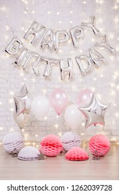 birthday party decoration - happy birthday letters air balloons, stars and paper balls over white brick wall with lights