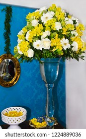 Birthday party decoration with jug with arrangement of white and yellow flowers