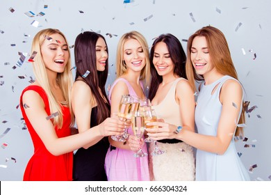 Birthday party. Excited fancy young ladies are toasting for birthday girl, having champagne, all in colorful trendy outfits, charming and cute. Shining glow confetti is all around
