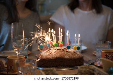 Birthday Party with the Family! Layed Table with heartshaped Cake and Many lighted Candles. Realistic Image