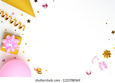 Birthday or party greeting card with copy space. Holiday frame or background with pink balloon, gift, confetti, star, gold carnival cap and streamer. Top view.