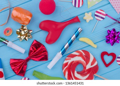 Birthday party items and accessories. Flat lay decorative supplies for party celebration on color wooden background.