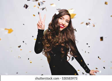 Birthday party, new year carnival. Young smiling woman on white background celebrating brightful event, wears elegant fashion black dress and yellow crown. Sparkling confetti, having fun, dancing