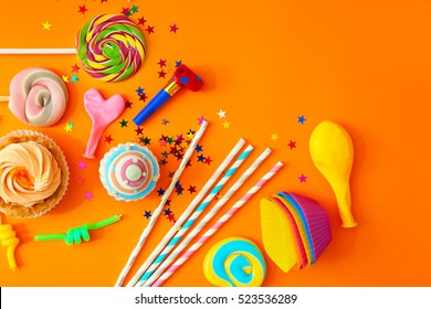 Birthday party objects on orange background, top view