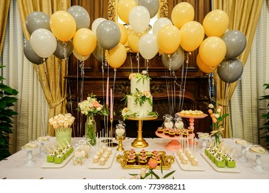 birthday party set up with fondant cake and coloured balloons