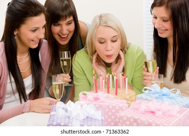 Birthday party - woman blowing candle on cake, champagne, presents