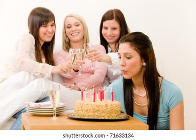 Birthday party - woman blowing candle on cake, champagne, toast