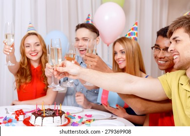 Birthday party. Young happy people wearing cone caps sitting at the table laughing holding and clinking glasses of champagne near the birthday cake