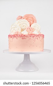 Birthday pink cake, decorated with meringue cookies on a white background.