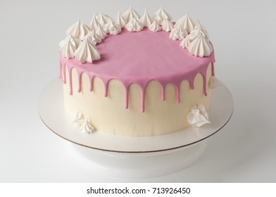 Birthday pink cake for girl, decorated with meringue cookies on a white background.
