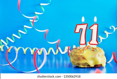 Birthday of seventy one years. Cupcake with white burning candle in the form of number 71. Vivid blue background with copy space