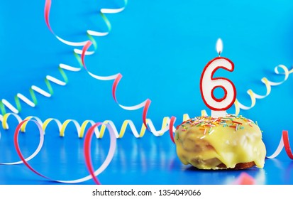Birthday of six years. Cupcake with white burning candle in the form of number 6. Vivid blue background with copy space