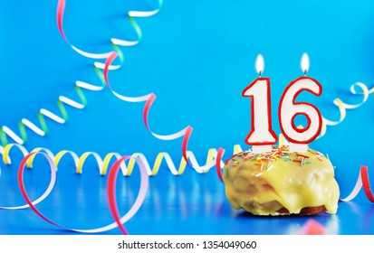 Birthday of sixteen years. Cupcake with white burning candle in the form of number 16. Vivid blue background with copy space