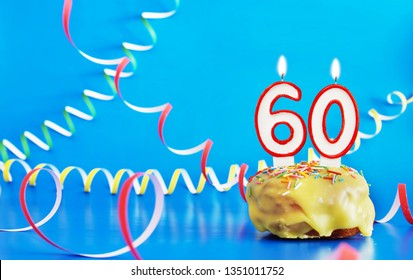Birthday of sixty years. Cupcake with white burning candle in the form of number 60. Vivid blue background with copy space